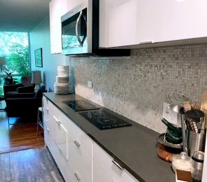 black countertop with white kitchen cabinets.