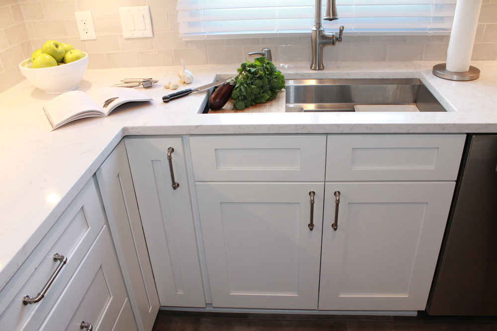stainless steel sink with white kitchen cabinets and countertop