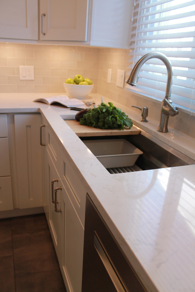 Kitchen sink with white kitchen cabinets and countertop