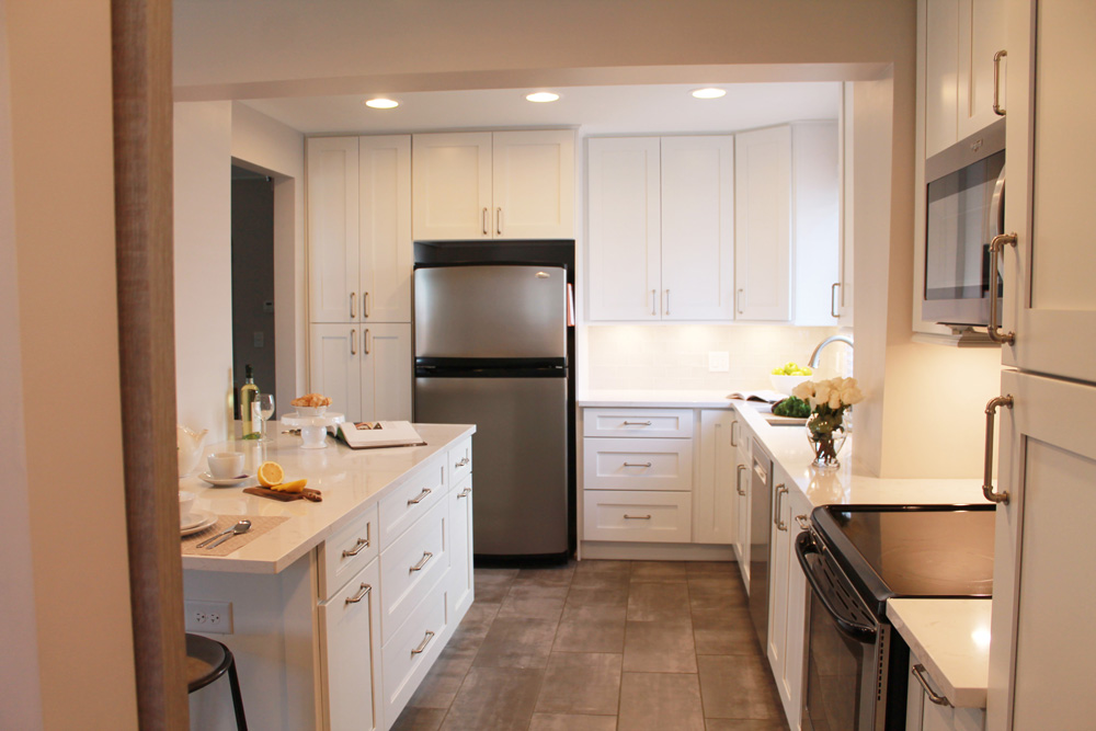 full kitchen with white cabinets and a white kitchen island