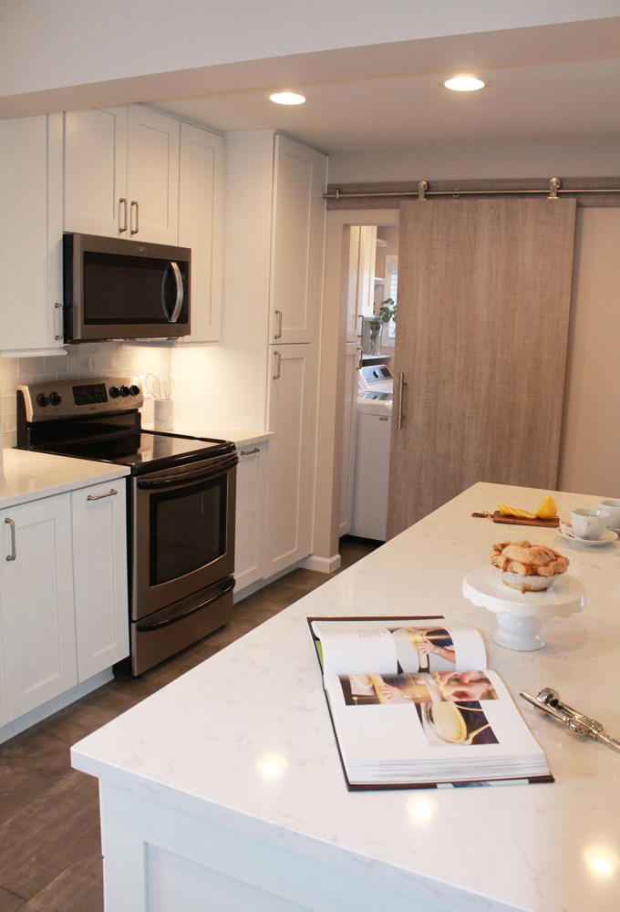 white kitchen with stainless steel microwave and stove