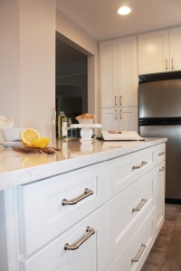 white kitchen island with granite countertop and kitchen cabinets