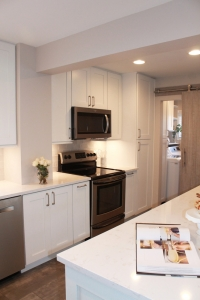 white kitchen with dishwasher, microwave and stove